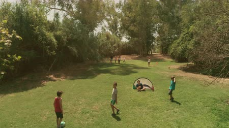 temporadas : Young happy kids in summer camp playing football soccer in green grass field children slow motion aerial vertical