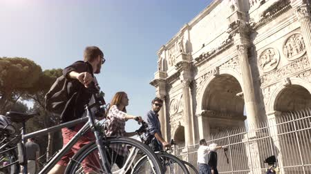 arch of constantine : Three young friends tourists walking with bikes near constantine arch at Colosseum in Rome city centre on sunny day slow motion camera steadycam ground shot