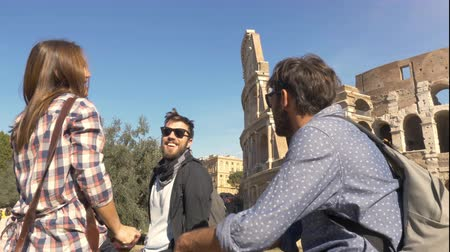 arch of constantine : Three young friends tourists sitting in front of colosseum in rome talking having fun near arch of constantine with backpacks sunglasses happy beautiful girl long hair Stock Footage