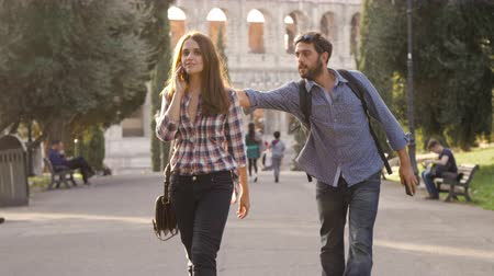 roma : Beautiful girl walks in park road talking on phone and attractive young man boyfriend behind her taps shoulder run funny prank trees colosseum in background in rome at sunset lovely beautiful woman with long hair slow motion Stok Video