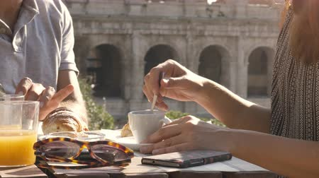 rzym : Happy young couple tourists having breakfast with coffee croissant cappuccino at bar restaurant outside in front of colosseum in rome at sunset close up shot