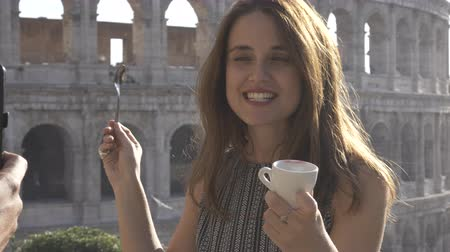 núpcias : Beautiful attractive young woman with long hair posing for pictures with cup of coffee in front of colosseum in rome at sunset FLAT NO GRADING