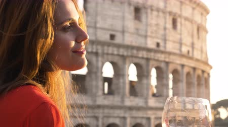 roma : Romantic elegant couple in love sitting at restaurant table in front of colosseum in rome at sunset with glass of red wine talking holding hands