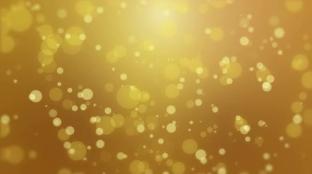 obiektyw : Glowing animated golden yellow bokeh background with floating light particles.