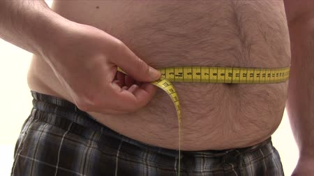 man eating : Measuring His Thick Belly Stock Footage