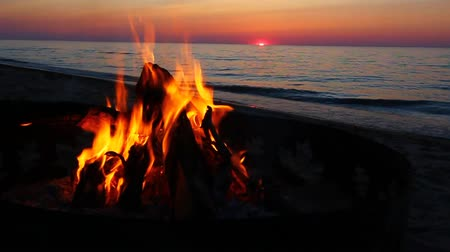 göl : Campfire burns brightly at sunset along the beautiful beach of Lake Superior in northern Michigan Stok Video