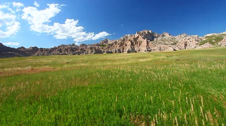 délre : Meadow grasses sway below the vast pinnacles and mountains of Badlands National Park - USA Stock mozgókép