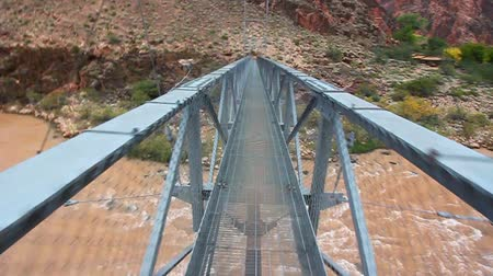 magasság : First person view of walking across a narrow bridge over the Colorado River in Grand Canyon National Park Stock mozgókép