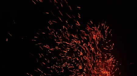 gyújtás : Sparks from a campfire dance through the cool night air