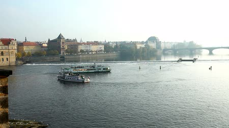 cseh : tourists ships motion on autumn river view from Prague bridge