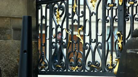 zamek : Metal fence on gate in cafedral yard and tourist walk at background Wideo
