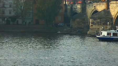 prague bridge : Pleasure boats move on vltava river in Prague autumn sunset Stock Footage