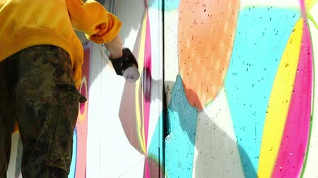 произведение искусства : View of young man drawing graffiti on wall with spray can