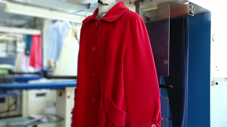clothing : View of laundry worker treated with steam red coat, close-up