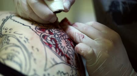tatuagem : View of master draws tattoo in red ink, close-up