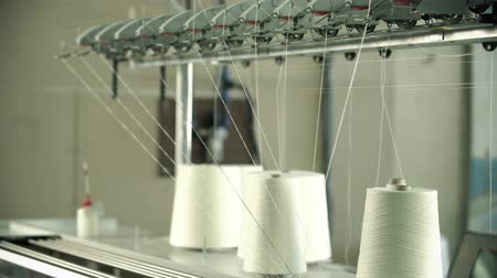 işlenmiş : White thread spools at rewinding machine video