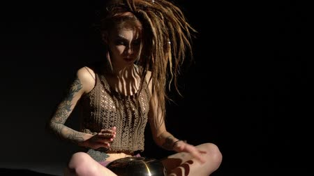 Blonde with dreadlocks playing tapidrum view