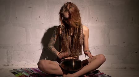Video of blonde with dreadlocks playing tapidrum