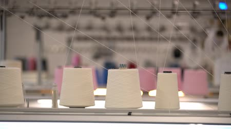 závit : Spools of white thread on knitting device view
