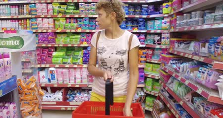 consumir : Girl chooses goods and meal in the supermarket. Shopping in the store. Young female is carefully analyzing products in a market. Stock Footage