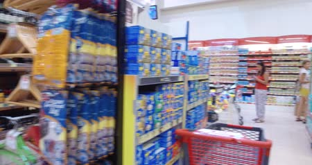 bakkal : Girl chooses goods and meal in the supermarket. Shopping in the store. Young female is carefully analyzing products in a market. Stok Video