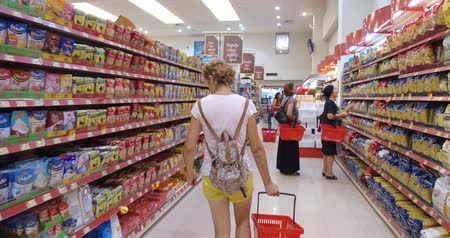 tüketmek : Girl chooses goods and meal in the supermarket. Shopping in the store. Young female is carefully analyzing products in a market. Stok Video