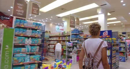 supermarket shelf : Girl chooses goods and meal in the supermarket. Shopping in the store. Young female is carefully analyzing products in a market. Stock Footage