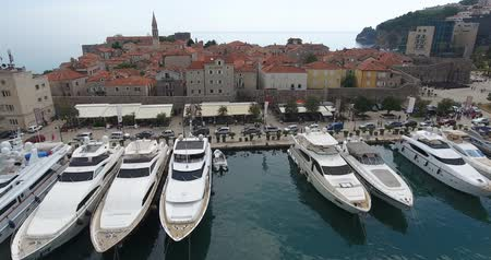 budva : Aerial view of Old Budva town and Budvas marina with its boats and yachts. Flight above the marina and waterfront, a lot of motorboats and yachts moored on the dock Stock Footage