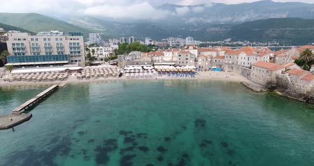kotor : Budva, Montenegro: Flying over the beach of Budva with its umbrellas and people who sunbathe and swim in the sea