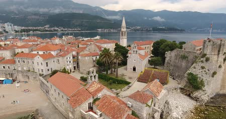 budva : Flight above the Old Town of Budva, Montenegro. Aerial view of Old Town Budva, red roofs of its stone houses in the traditional Balkan style, ancient church and a seashore with boats Stock Footage