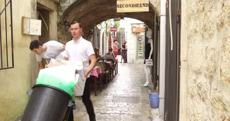 проведение : Budva, Montenegro, September 10, 2018: Two young guys, cafe workers, clean and take out the garbage in big bags