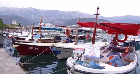 balcani : Budva, Montenegro - October 06, 2018: ?oast of the Adriatic sea. Fishing boats are moored on the waterfront near the Old Town of Budva. In the background you can see the picturesque mountains