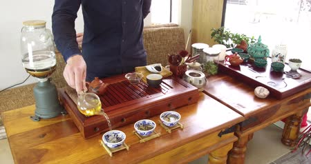 fabricado cerveja : Chinese tea tasting in the tea shop. Tea seller, dressed in european, brews Chinese tea for tasting. Chinese tea set, traditional chinease teapot and cups on bamboo mats