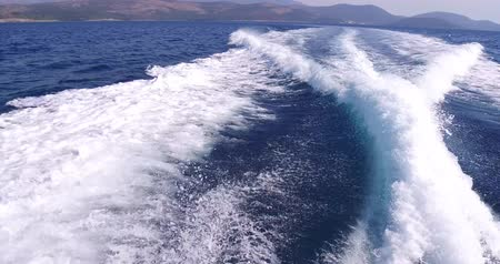 navigation : On board side view of a yacht navigating on blue sea vawes. Luxury yacht floats on blue sea waves. Sailing in the wind through the waves