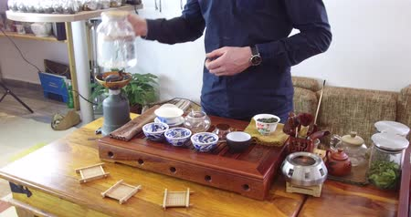 cooking pots : Chinese tea tasting in the tea shop. Tea seller, dressed in european, brews Chinese tea for tasting. Chinese tea set, traditional chinease teapot and cups on bamboo mats