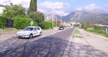 varoşlarda : Bar, Montenegro, April, 17, 2016: Road traffic in Montenegro. Cars, trucks and motorcycles. Sky is blue, its a sunny day. Mountains on the background
