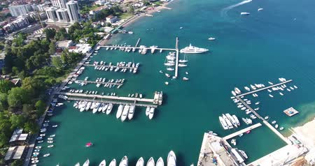 парусное судно : Aerial view of Budvas marina with its boats, yachts and ships. Flight above the marina and the waterfront moored at the pier Стоковые видеозаписи