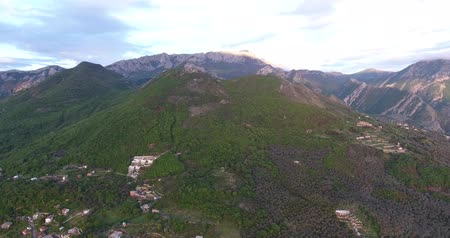 yalan : Aerial quadcopter shot of an untouched forests and roads between them high in the mountains in south Montenegro. The sun illuminates the top of the mountain