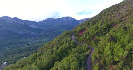 érintetlen : Aerial quadcopter shot of an untouched forests and roads between them high in the mountains in south Montenegro. The sun illuminates the top of the mountain