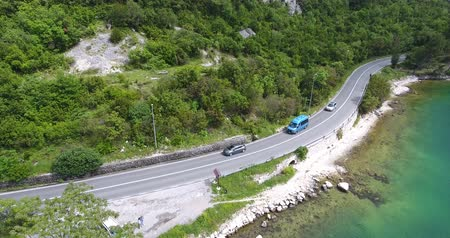 沿岸の : The quadcopter is flying over the sea shore. We can see the turquoise and the seashore. Cars, trucks and tourist buses are driving along the road