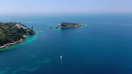 hajózik : Aerial shot, quadcopter flies along the rocky seashore, The sea water is turquoise, clean and clear