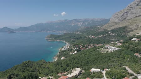 Drone flies above the coastline of the Adriatic sea, southern Montenegro, in a sunny summer day. Water in the sea is turquoise, clean and clear Stok Video
