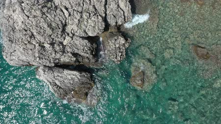 boulders : Sea waves roll against coastal cliffs and stones. Sea water is clear and turquoise. Sunny summer day on the shores of the warm southern sea Stock Footage