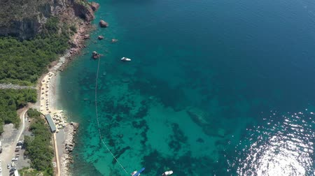 Aerial shot, drone flying over a sandy sea beach with sun umbrellas. The water in the sea is clear, emerald green and transparent, sunlight is reflected in the water. Near the shore, small white boats swing on the waves Stok Video