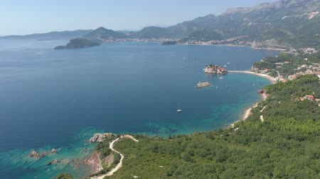 Aerial shot of a sea coast, small island in the sea and mountains Stok Video