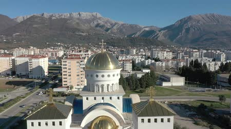 Aerial view of orthodox ?athedral with big golden domes - main church in Bar town, Montenegro. 4K drone panning shot of Balkans cityscape on sunny day