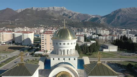 upward : Aerial view of orthodox ?athedral with big golden domes - main church in Bar town, Montenegro. 4K drone panning shot of Balkans cityscape on sunny day