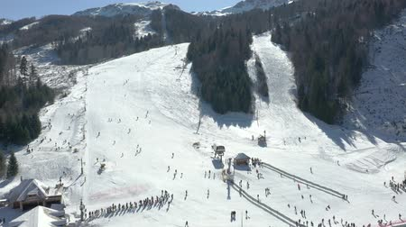 upward : Aerial video shooting of a ski resort, a view of the mountain where the lift and descent are located, a lot of skiers go skiing down the mountain Stock Footage