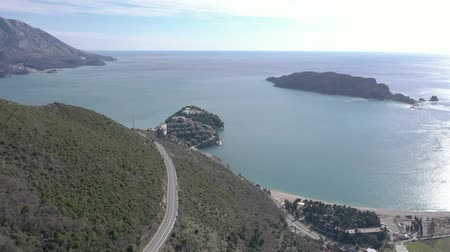 Aerial video shooting of a narrow winding mountain road where cars are driving. On the right you can see the blue sea with small islands Stok Video