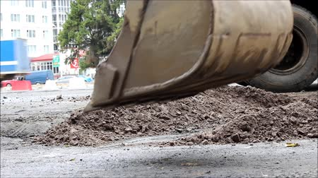 bailer : excavator bucket, which leveled the ground in preparation for road asphalting Stock Footage